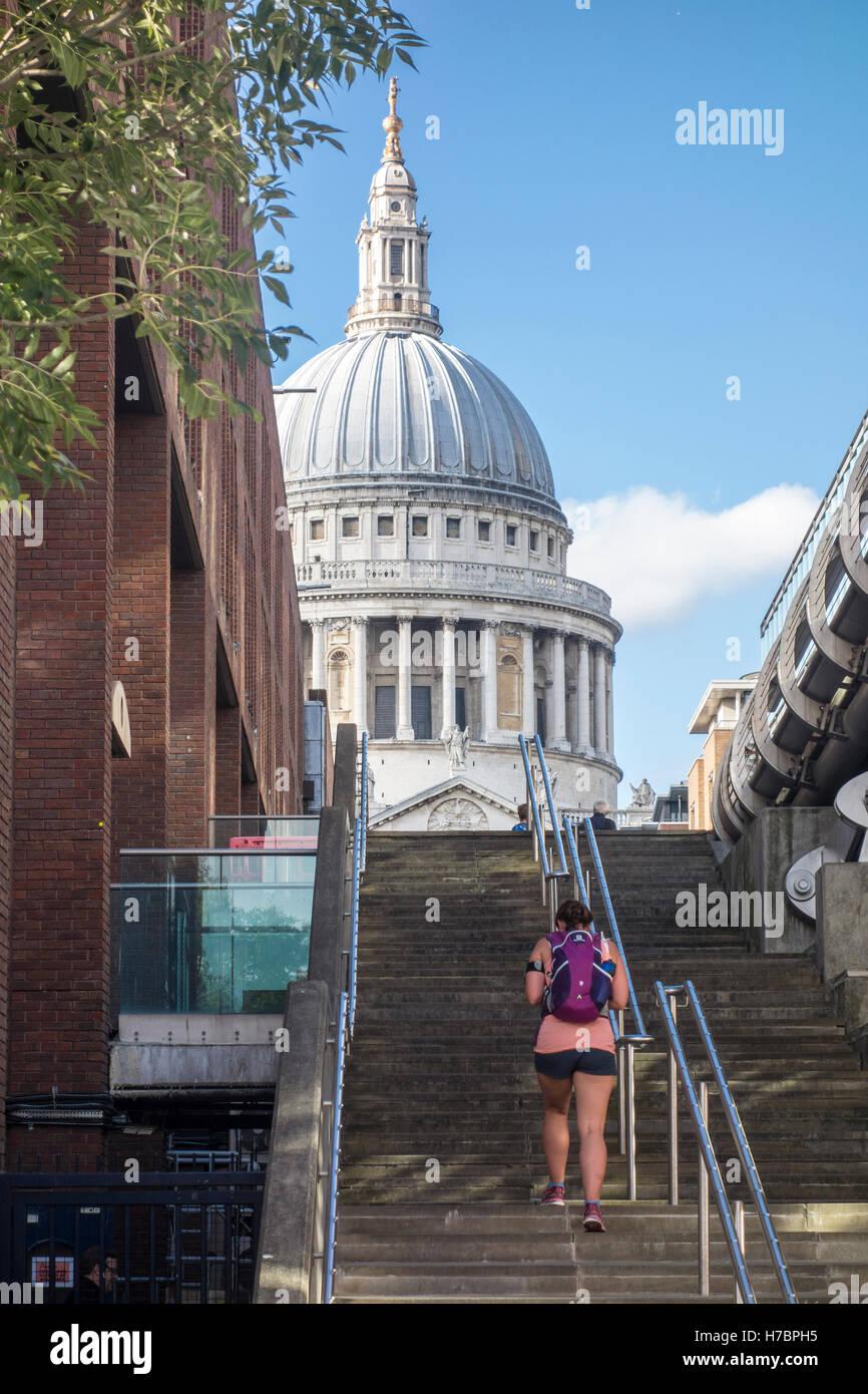 Giovani femmine pareggiatore fino a piedi i passi accanto al Millennium Bridge verso la Cattedrale di St Paul. Città Immagini Stock