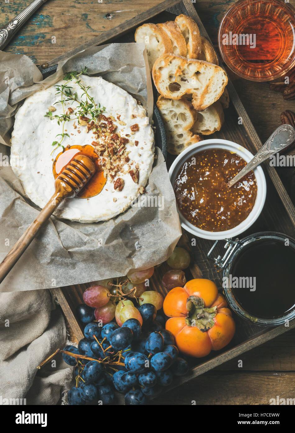 Formaggi, Frutta e Vino. Camembert in pentola con i dadi e le erbe aromatiche, uva, persimmon, fig marmellata, miele, Immagini Stock