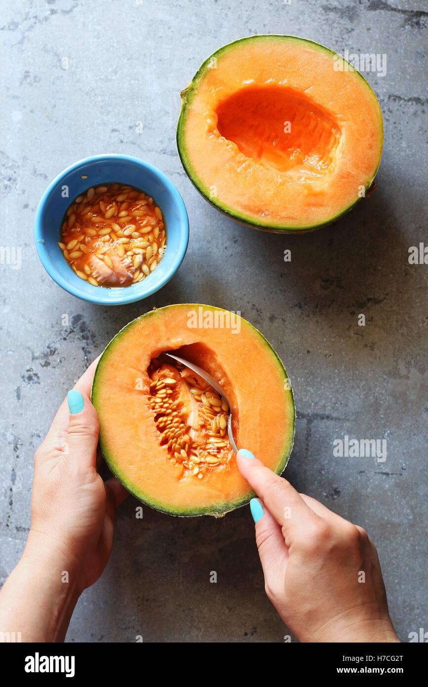 Femmina di movimentazione a mano i semi da un melone.vista superiore Immagini Stock