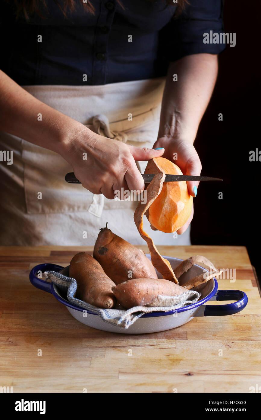 Femmina arancione di pelatura patate dolci. Immagini Stock