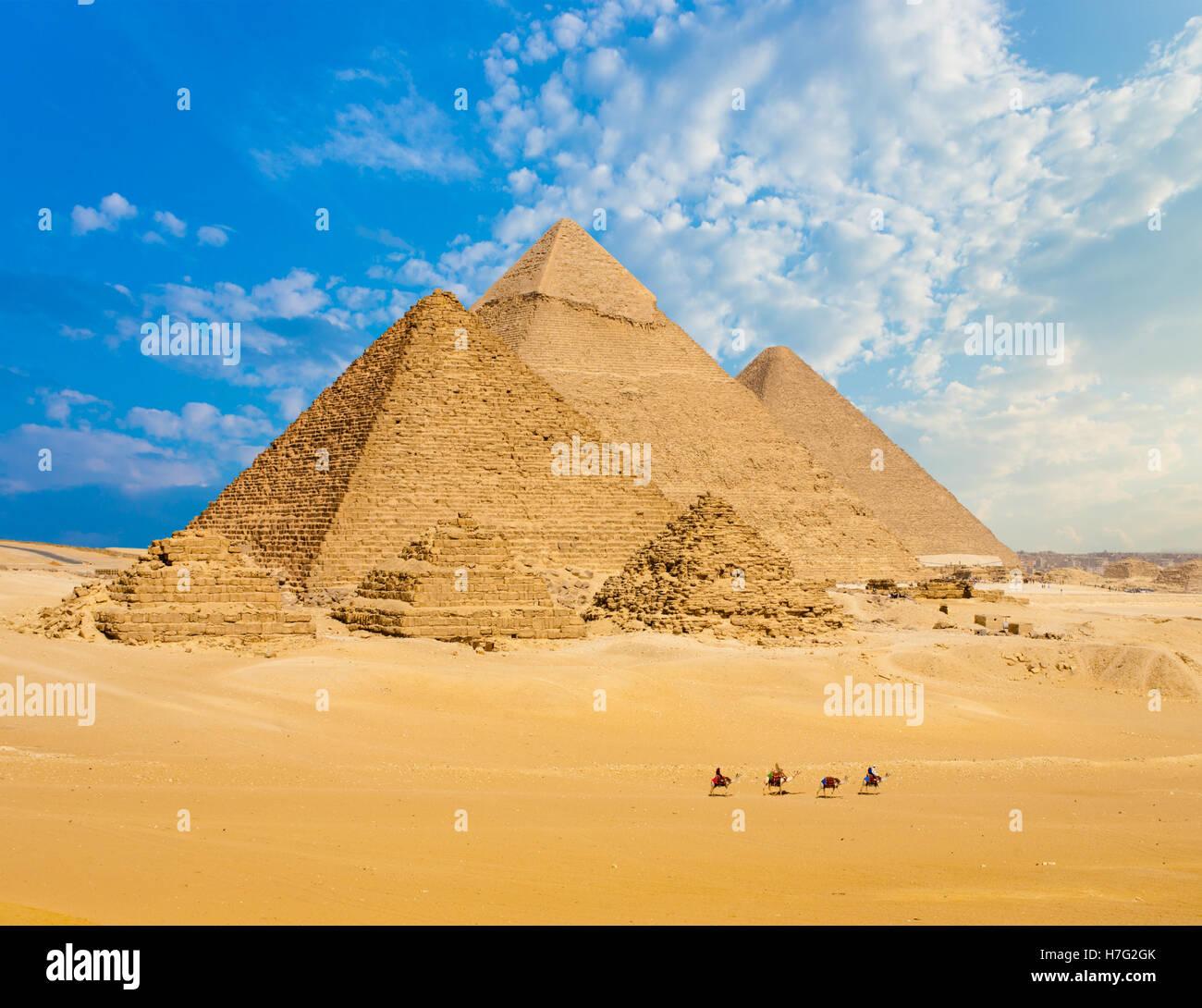 Tutte le piramidi egiziane a distanza con fila di cammelli a piedi in primo piano in Giza, Cairo, Egitto. Teleobiettivo Immagini Stock