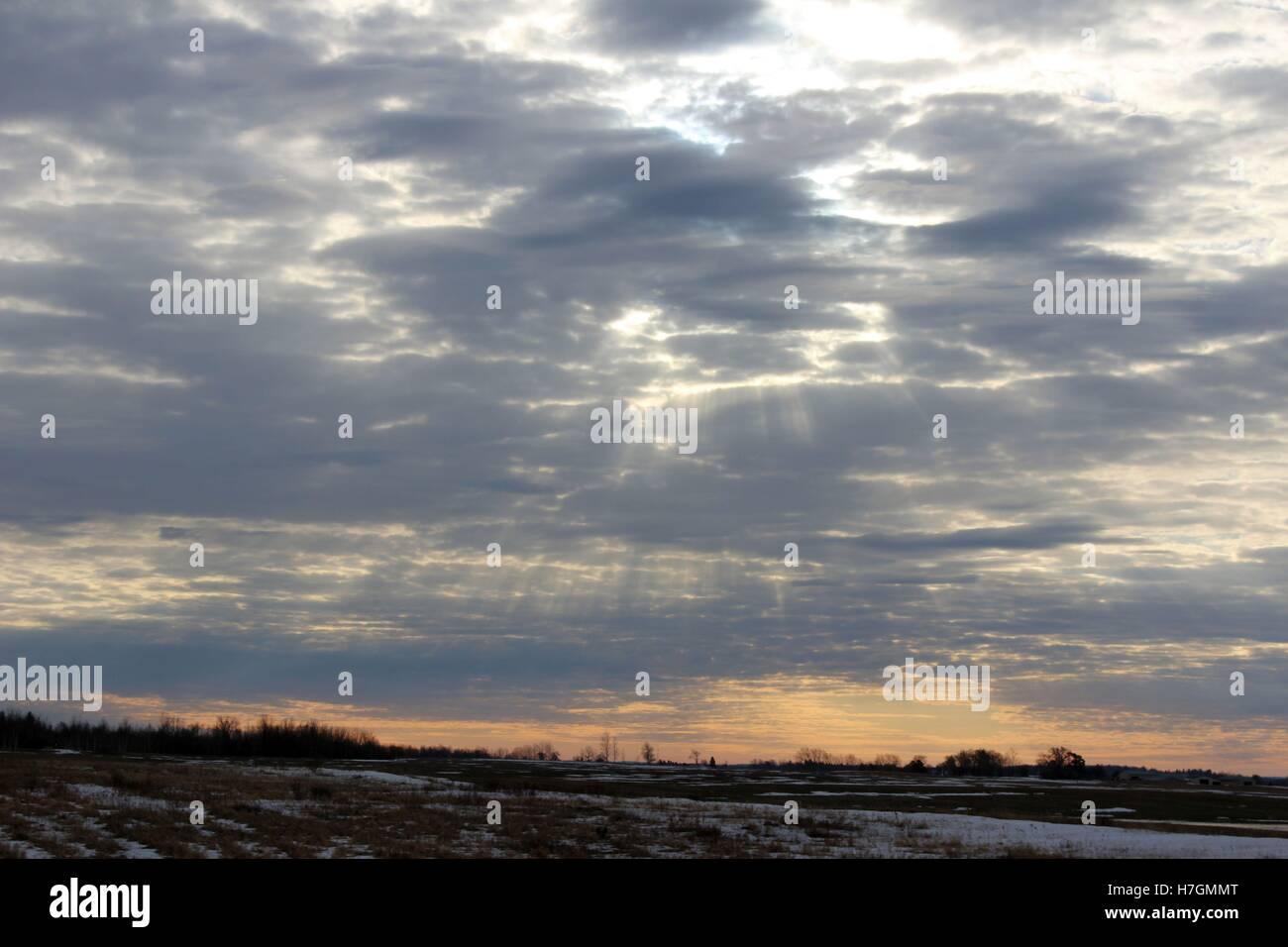 Raggi di sole risplendere fuori da dietro le nuvole scure Immagini Stock