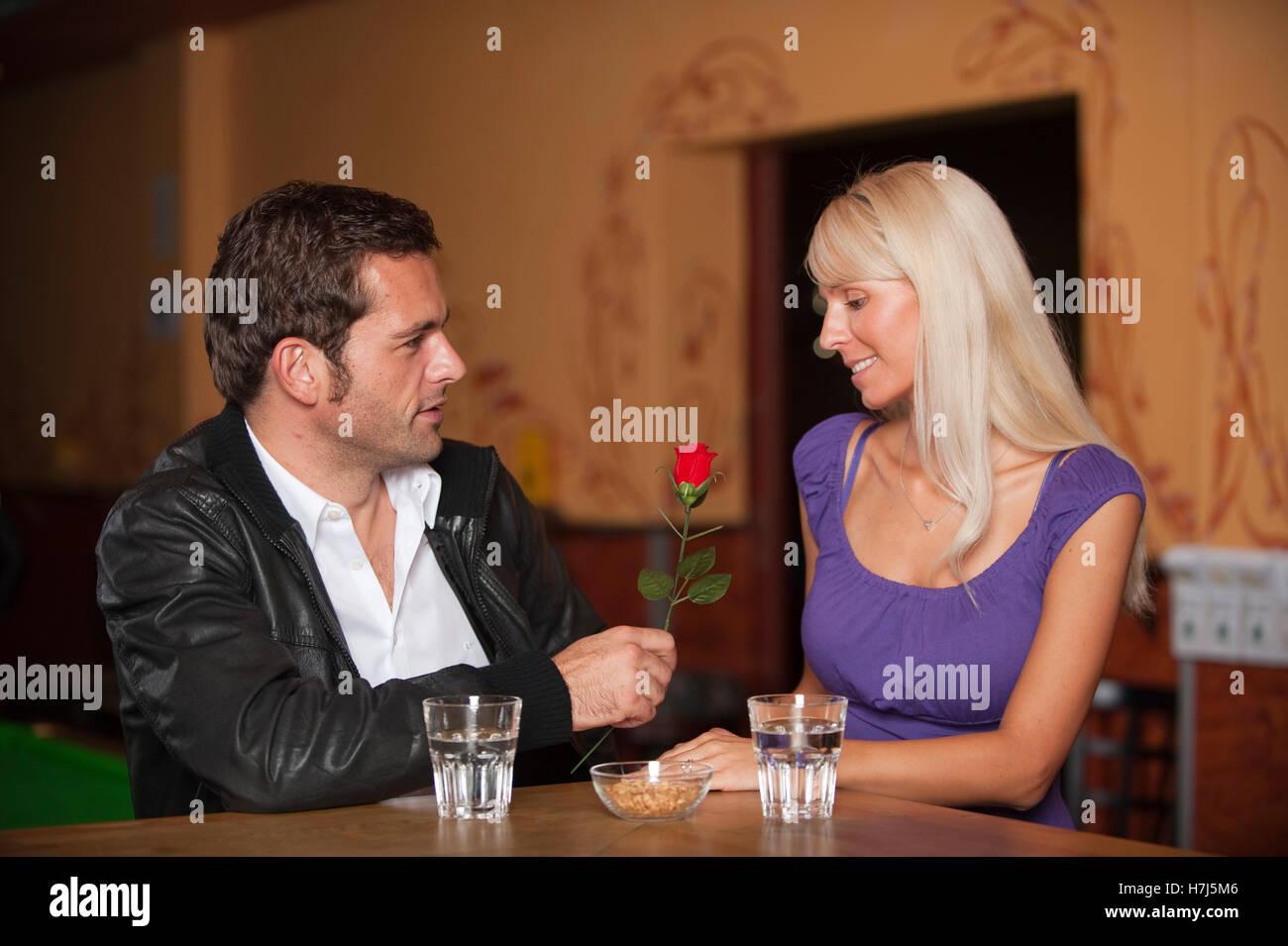 La data, l uomo e la donna con una rosa rossa al bar Foto Stock