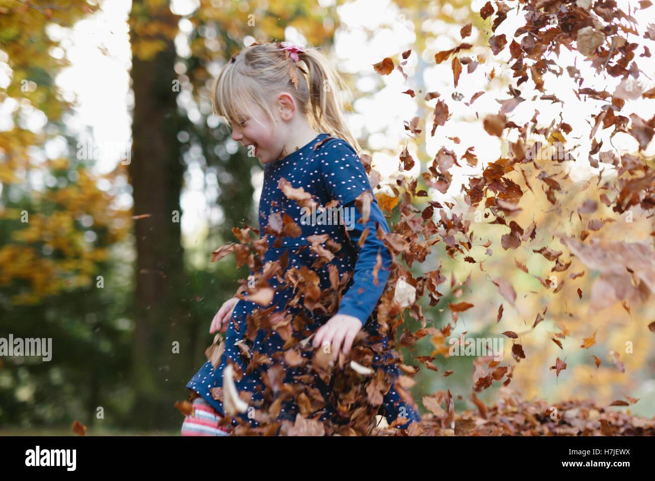 Felice l'autunno. Bambina giocando in foglie secche palo in autunno park. Immagini Stock