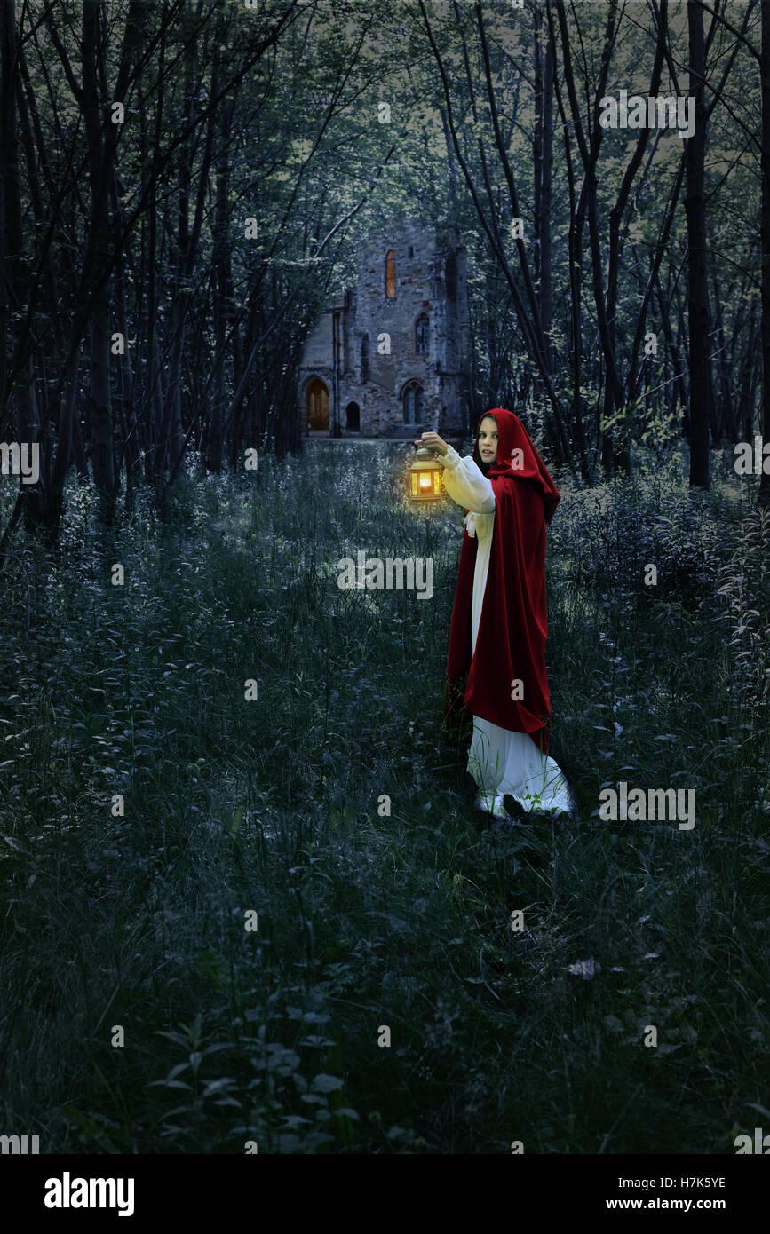 Donna con lanterna in foresta e castello Immagini Stock