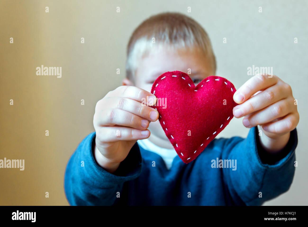 Cuore rosso nelle mani del bambino, fatto a mano regalo, il giorno di san valentino, di bontà e di amore familiare Immagini Stock