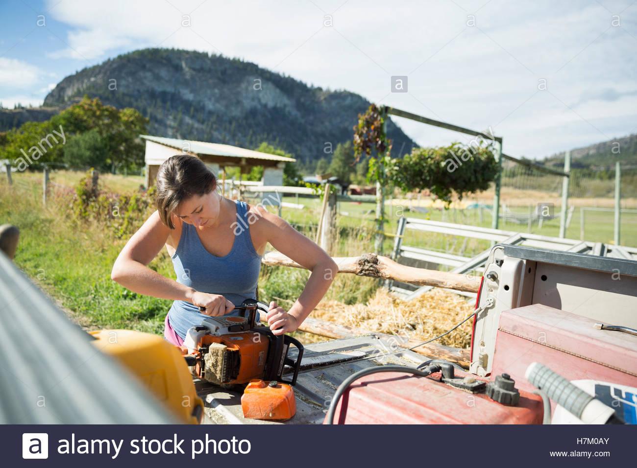 L'agricoltore femmina attrezzature di fissaggio sul pianale di sunny farm Immagini Stock