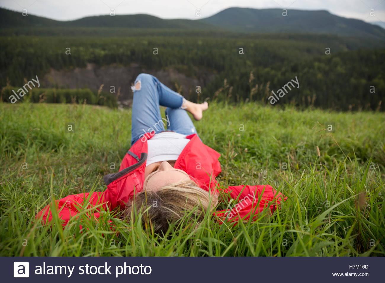 La donna posa rilassante in erba in remoto campo rurale Immagini Stock