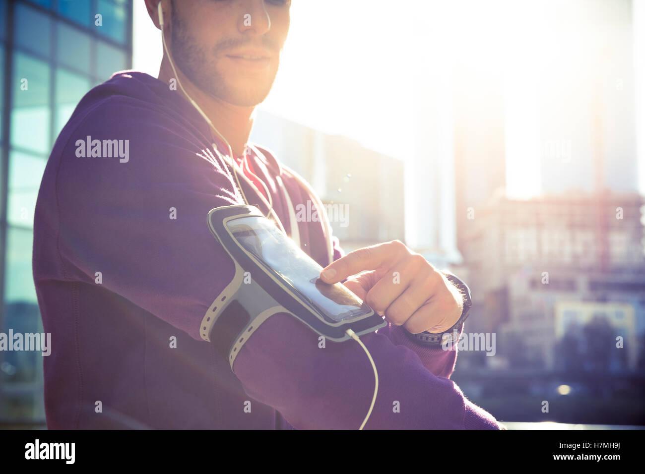 Esecuzione di allenamento uomo che ascolta la musica con il lettore mp3 di fascia da braccio o smart telefono cellulare. Immagini Stock