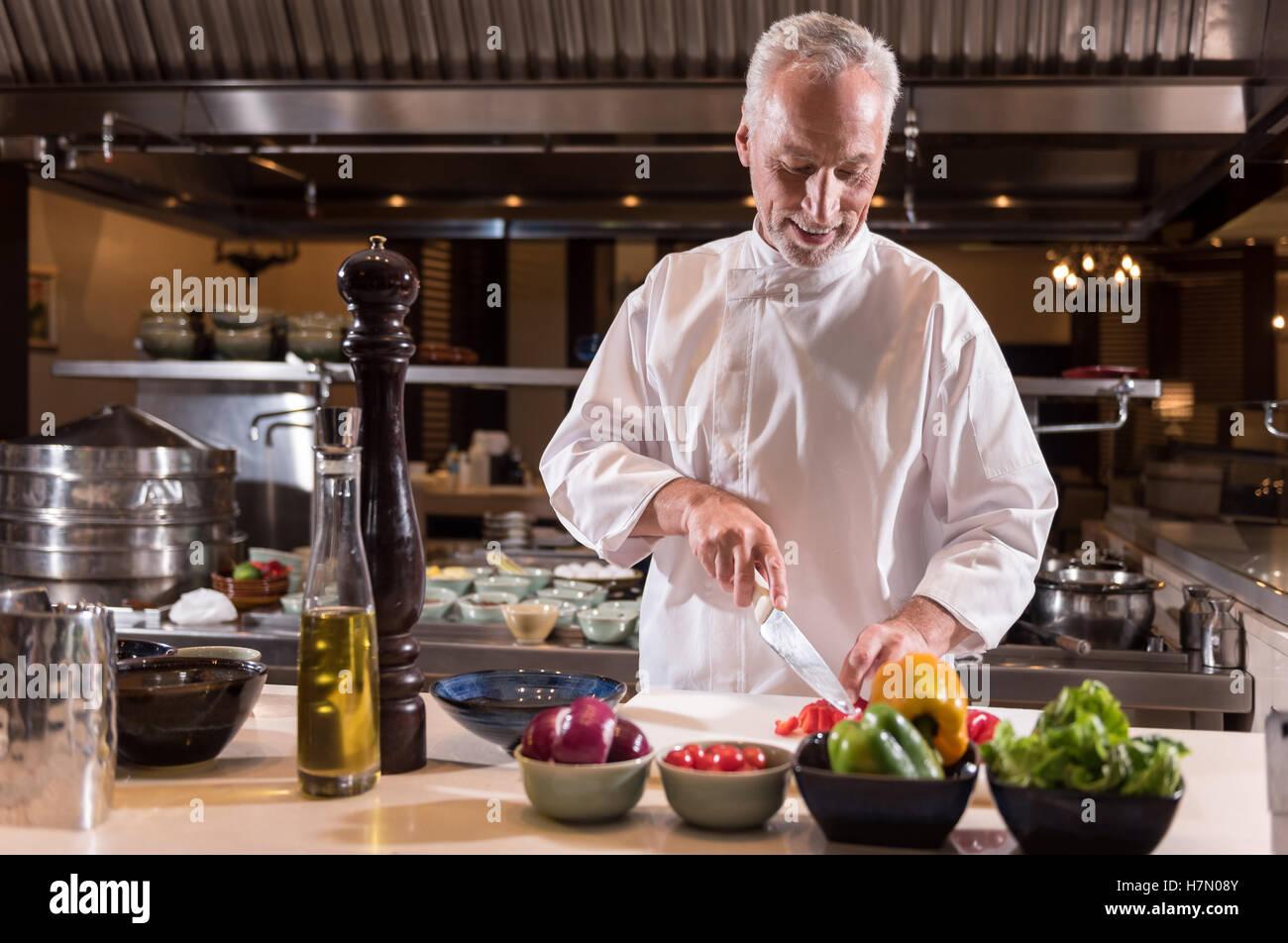 Lo chef felice il taglio della carta nella cucina del ristorante Immagini Stock