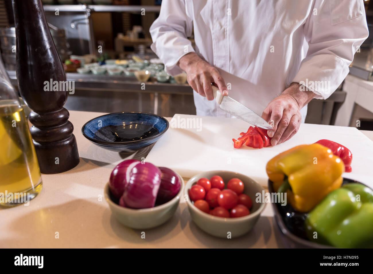 Forti mani dello chef il taglio della carta in cucina Immagini Stock