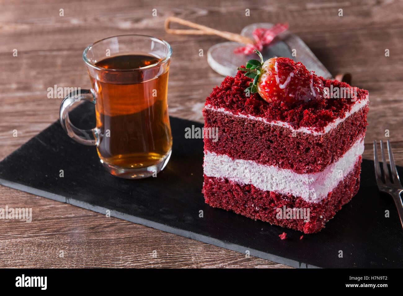 Fetta di torta rossa del velluto con glassa bianca è guarnito con fragole close up Immagini Stock