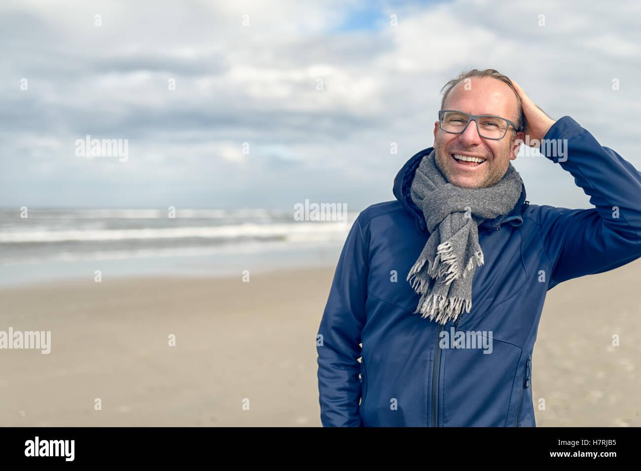 Felice di ridere uomo di mezza età con gli occhiali e una lana lavorata a maglia Sciarpa in piedi su una deserta Immagini Stock