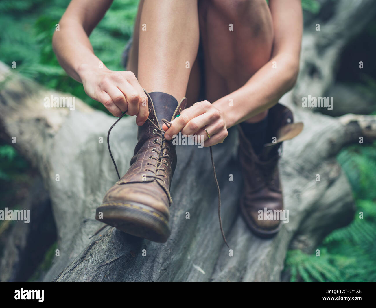 Una giovane donna è seduta su un registro nella foresta e legatura è il suo stivali Immagini Stock
