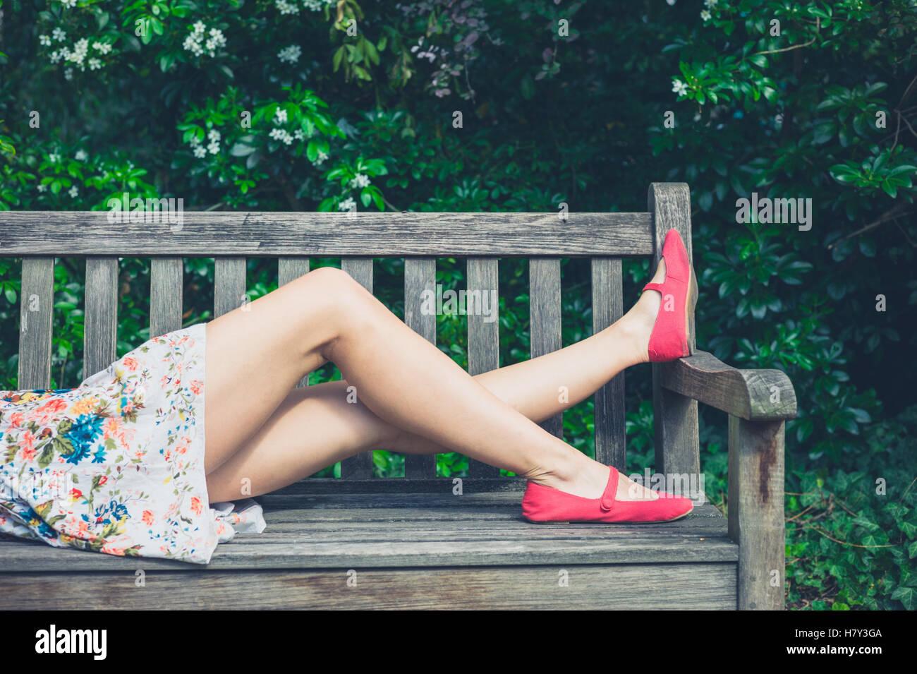 Una giovane donna che indossa un vestito estivo è rilassante su una panchina nel parco in una giornata di sole Immagini Stock