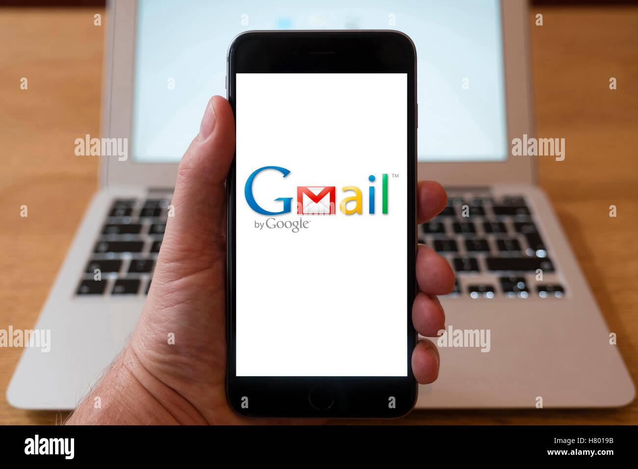 Utilizzo di iPhone smartphone per visualizzare il logo di Gmail , Google il servizio di posta elettronica Immagini Stock