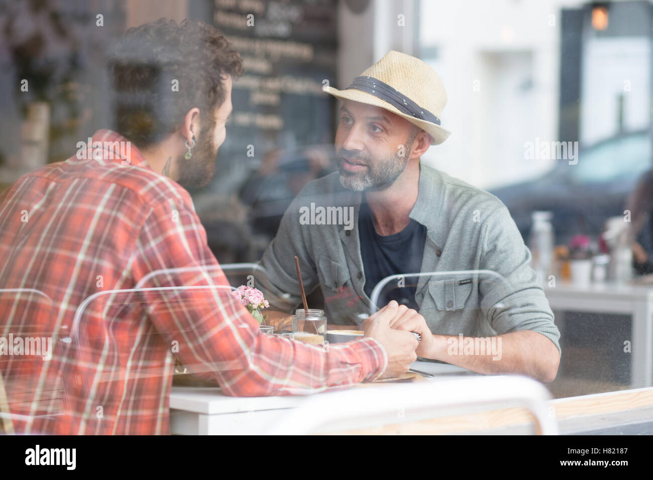 Coppia gay sat holding hands in cafe Immagini Stock