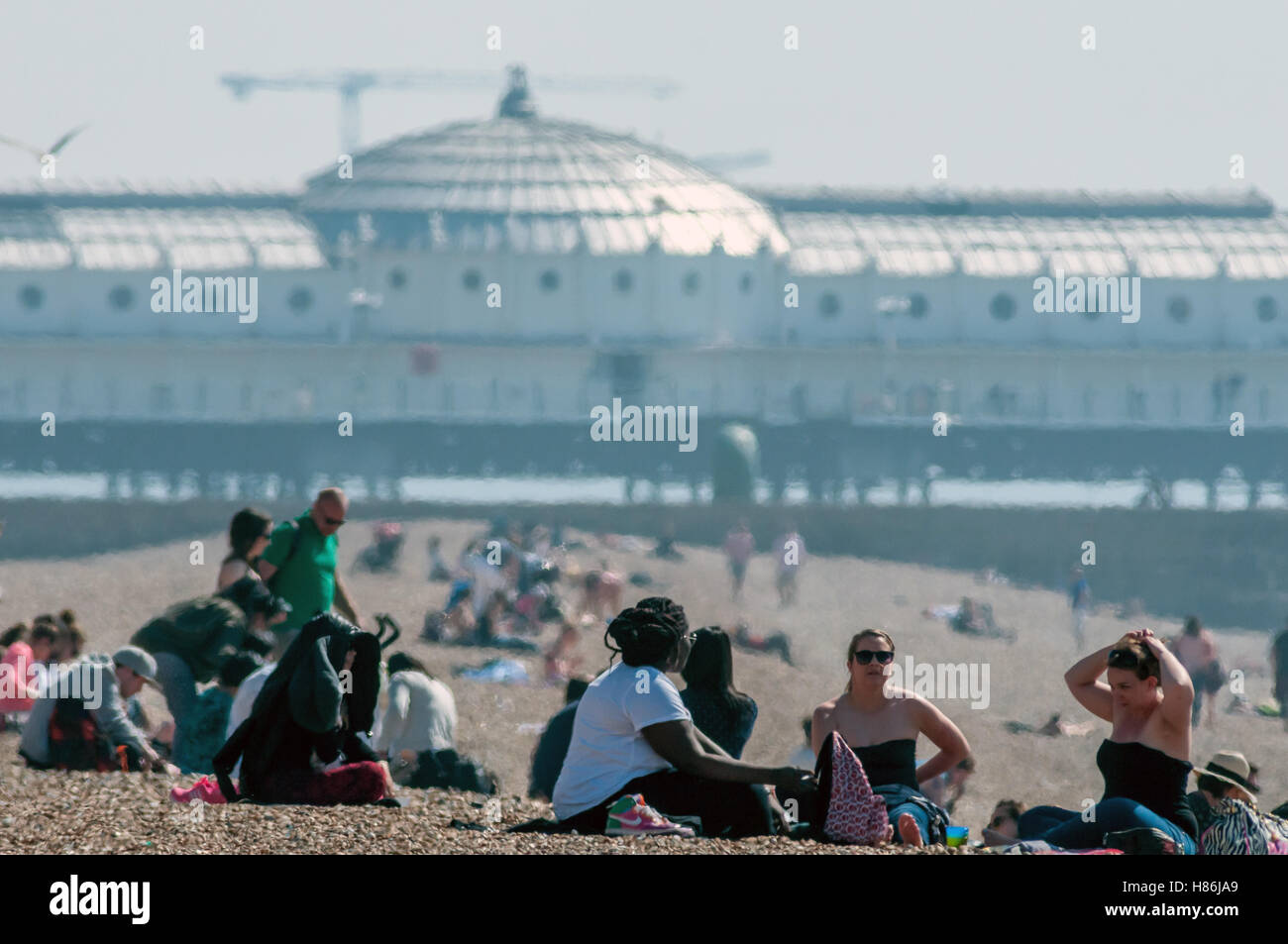 Le persone che si godono la molla del meteo sulla spiaggia di Brighton Immagini Stock