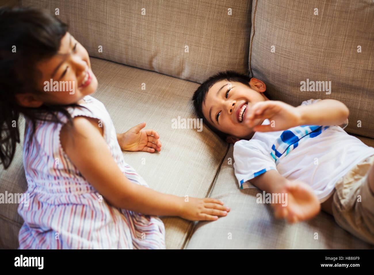 Casa di famiglia. Due bambini che giocano sul pavimento, sogghignando. Foto Stock