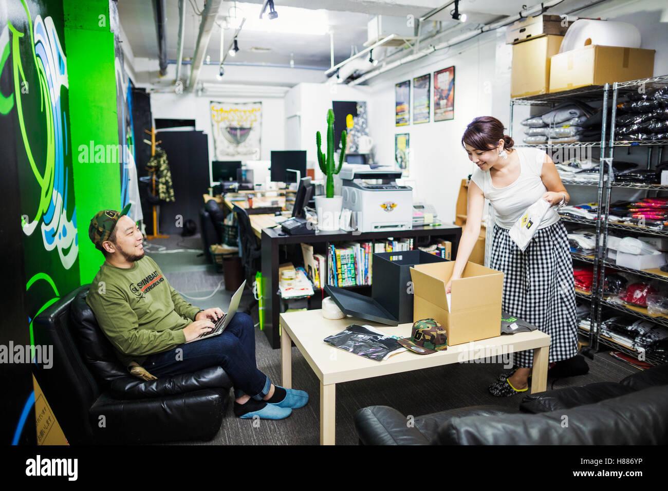 Design Studio. Due colleghi, l uomo e la donna, l'inventario e l'imballaggio di merci per la vendita e la Immagini Stock