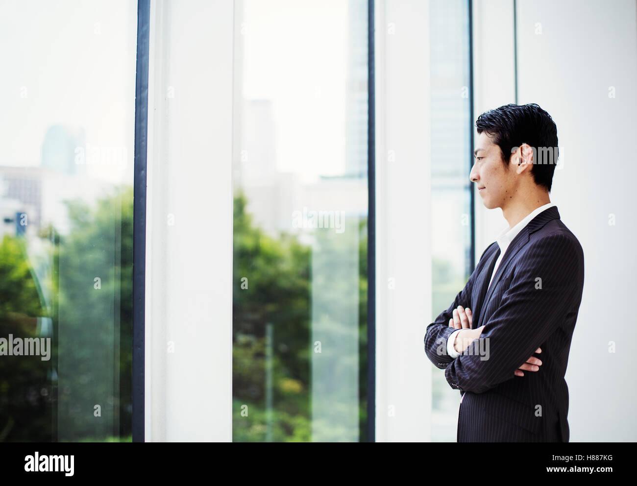 Un imprenditore in ufficio, da una grande finestra che guarda fuori. Immagini Stock