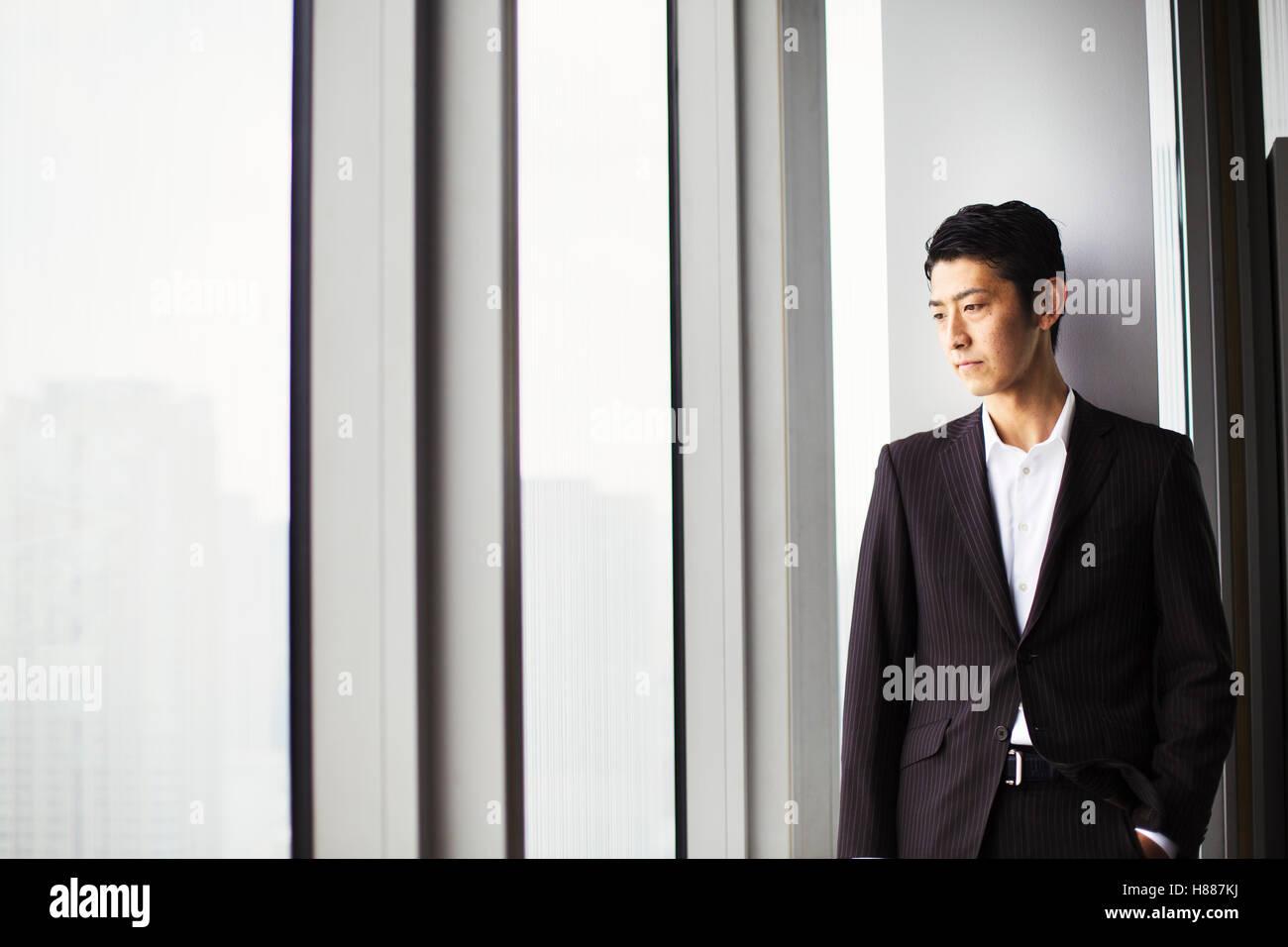 Un imprenditore in ufficio, da una grande finestra che si affaccia sulla città. Immagini Stock