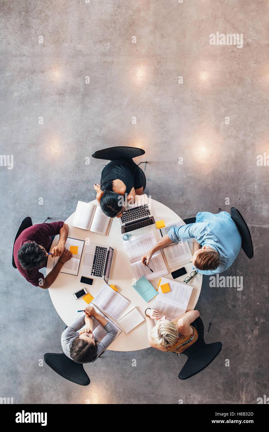 Gruppo di studenti che studiano insieme. Alta angolazione dei giovani seduti a tavola e a studiare con libri e laptop Immagini Stock