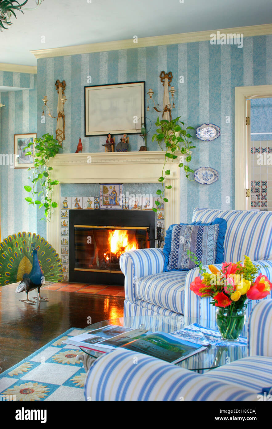 Camino con focolare aperto e poltrone a strisce blu in salotto ...