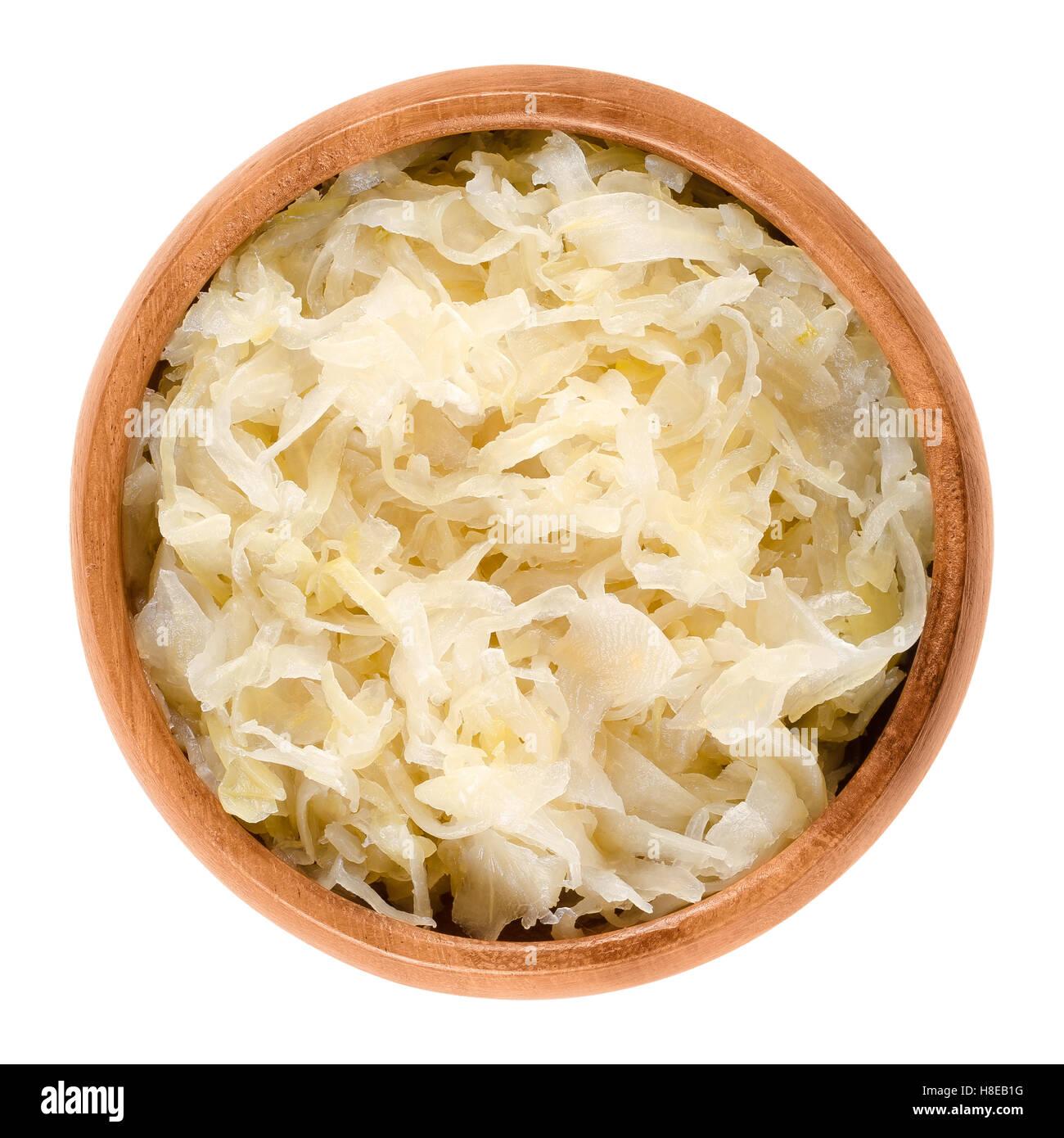 Il tedesco sauerkraut in ciotola di legno su bianco. Tagliare finemente il cavolo, fermentato dai batteri di acido Immagini Stock