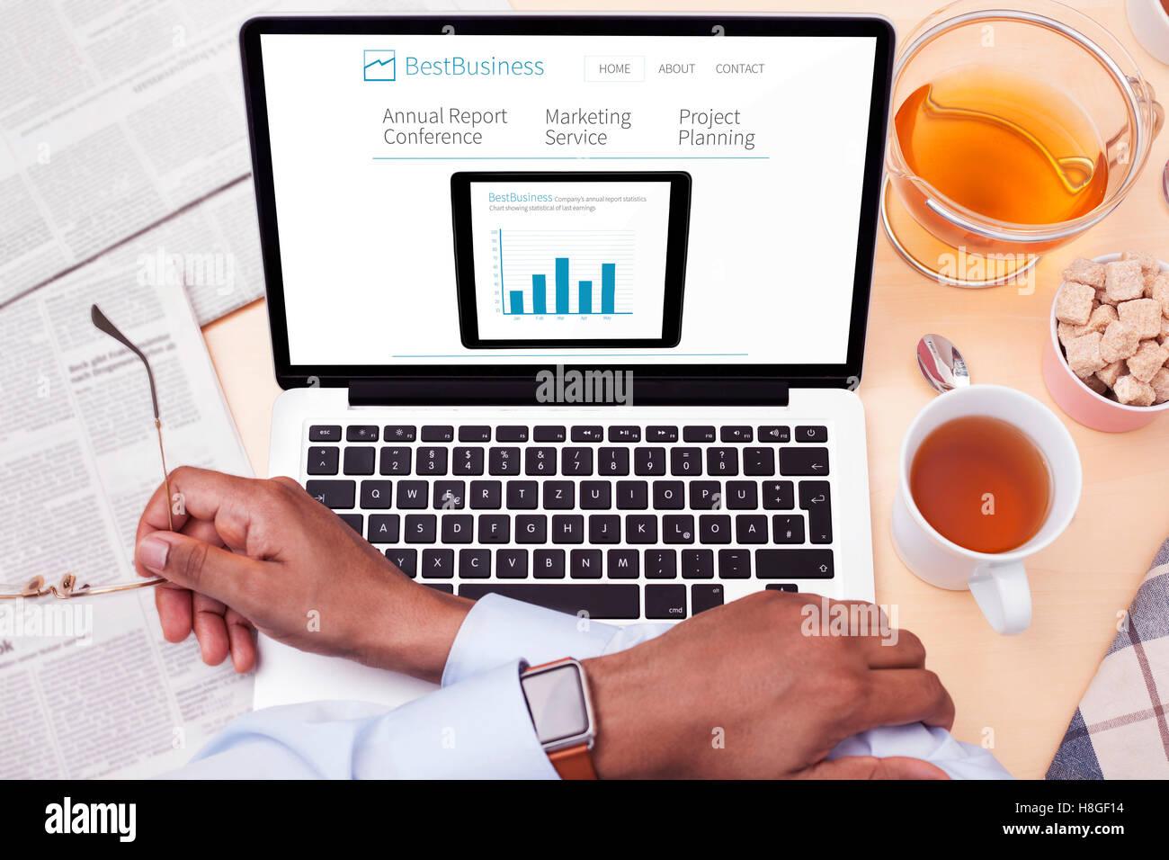 Computer responsivo sul tavolo bianco - sito web aziendale Immagini Stock