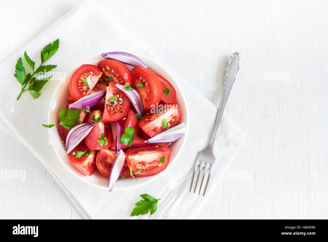 Insalata di pomodoro con cipolla, prezzemolo e pepe nero in vaso - sano vegetariano vegano antipasto alimentare Immagini Stock