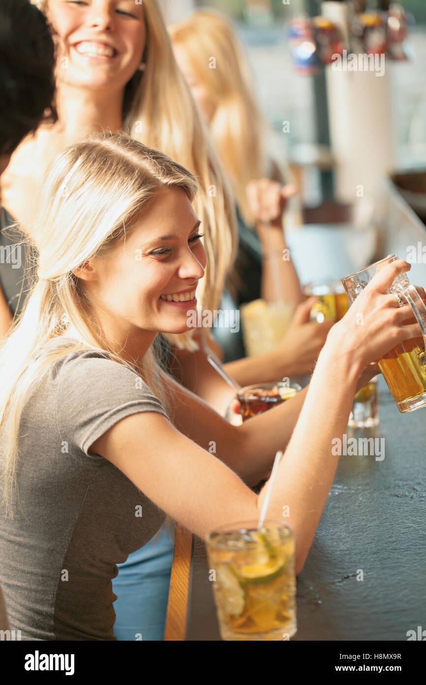 Donna bionda bere birra nel bar Immagini Stock