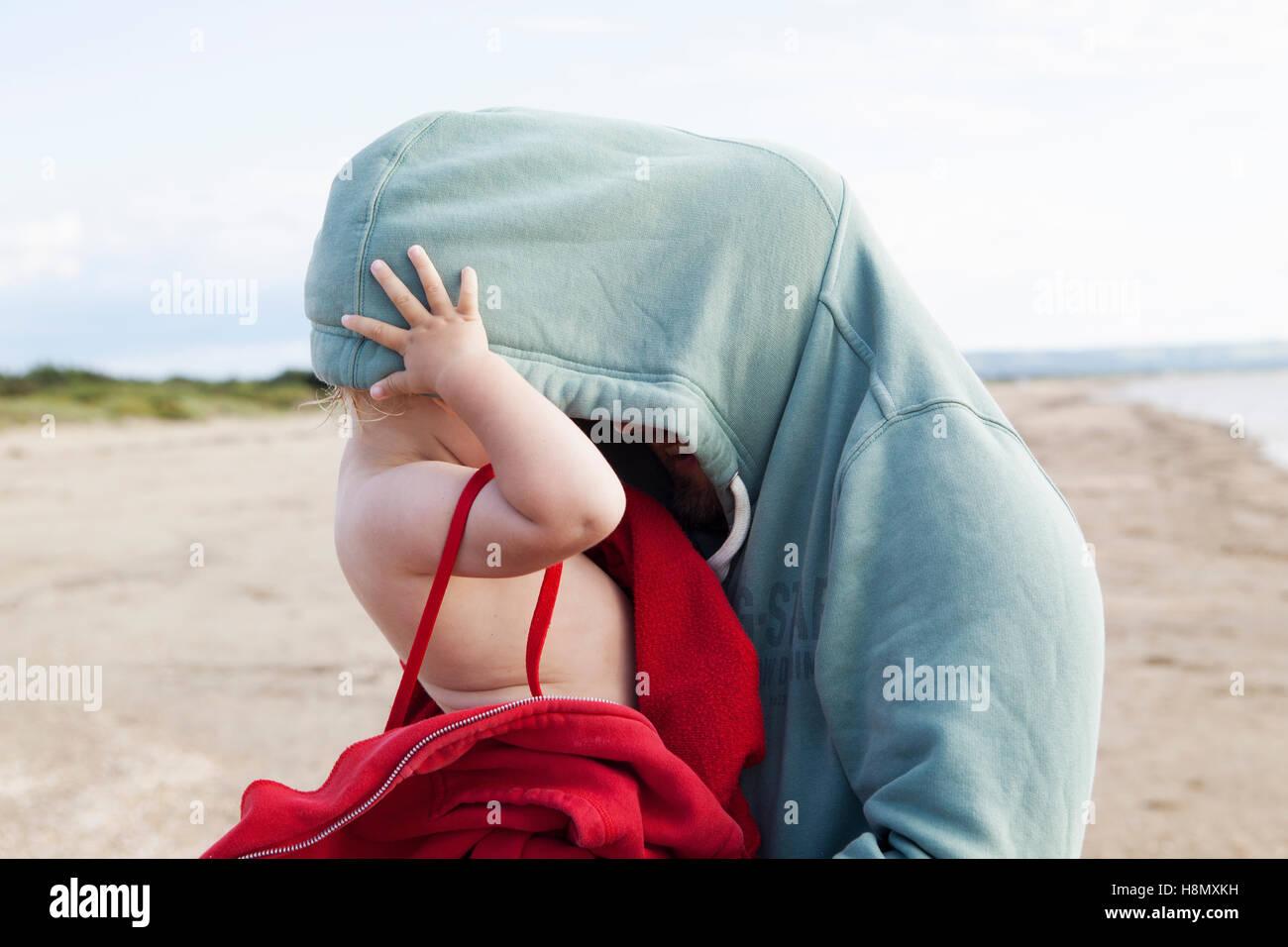 La ragazza (2-3) nascondere nel padre maglietta con cappuccio Immagini Stock