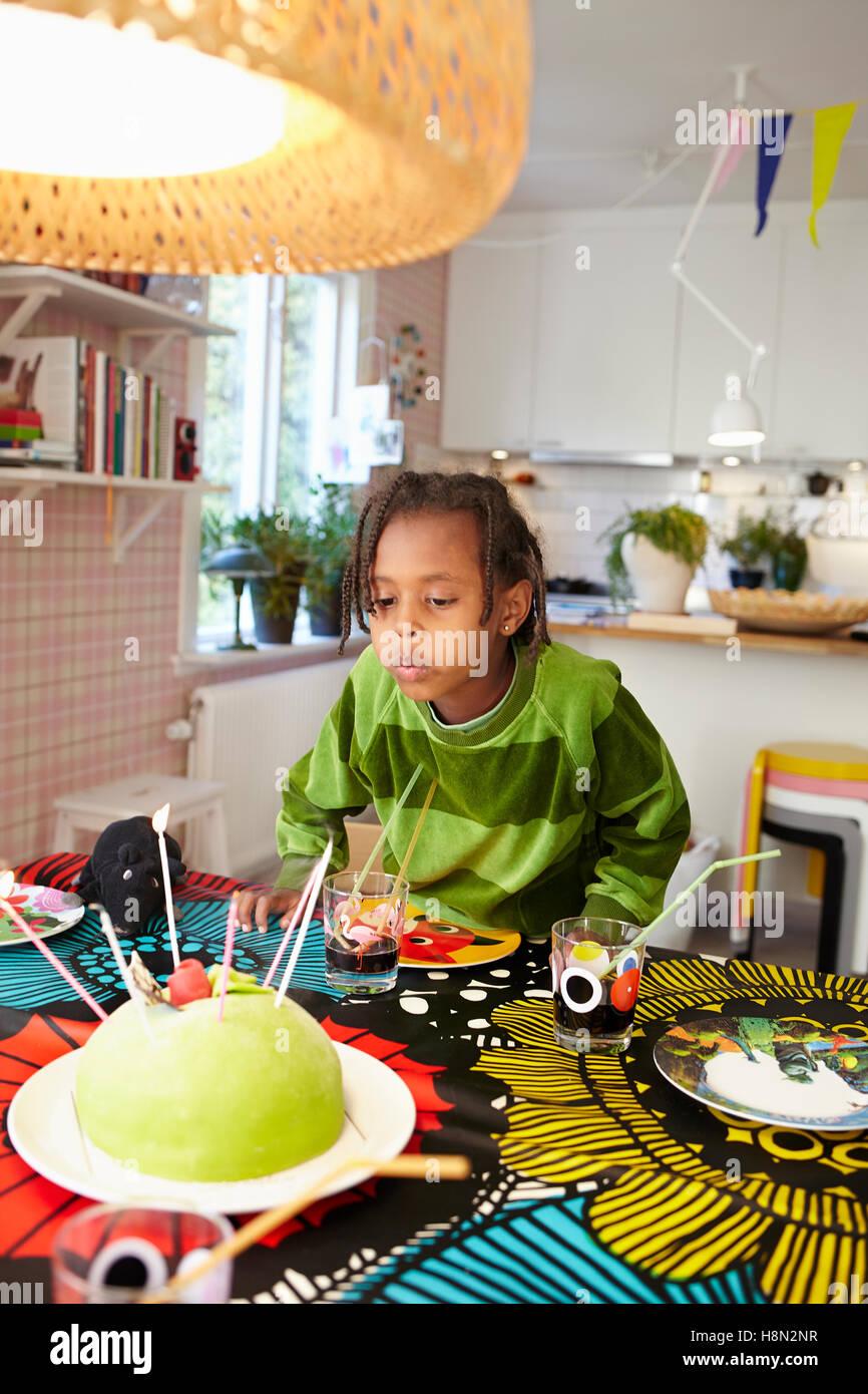La ragazza (6-7) soffiaggio candele sulla torta di compleanno Immagini Stock