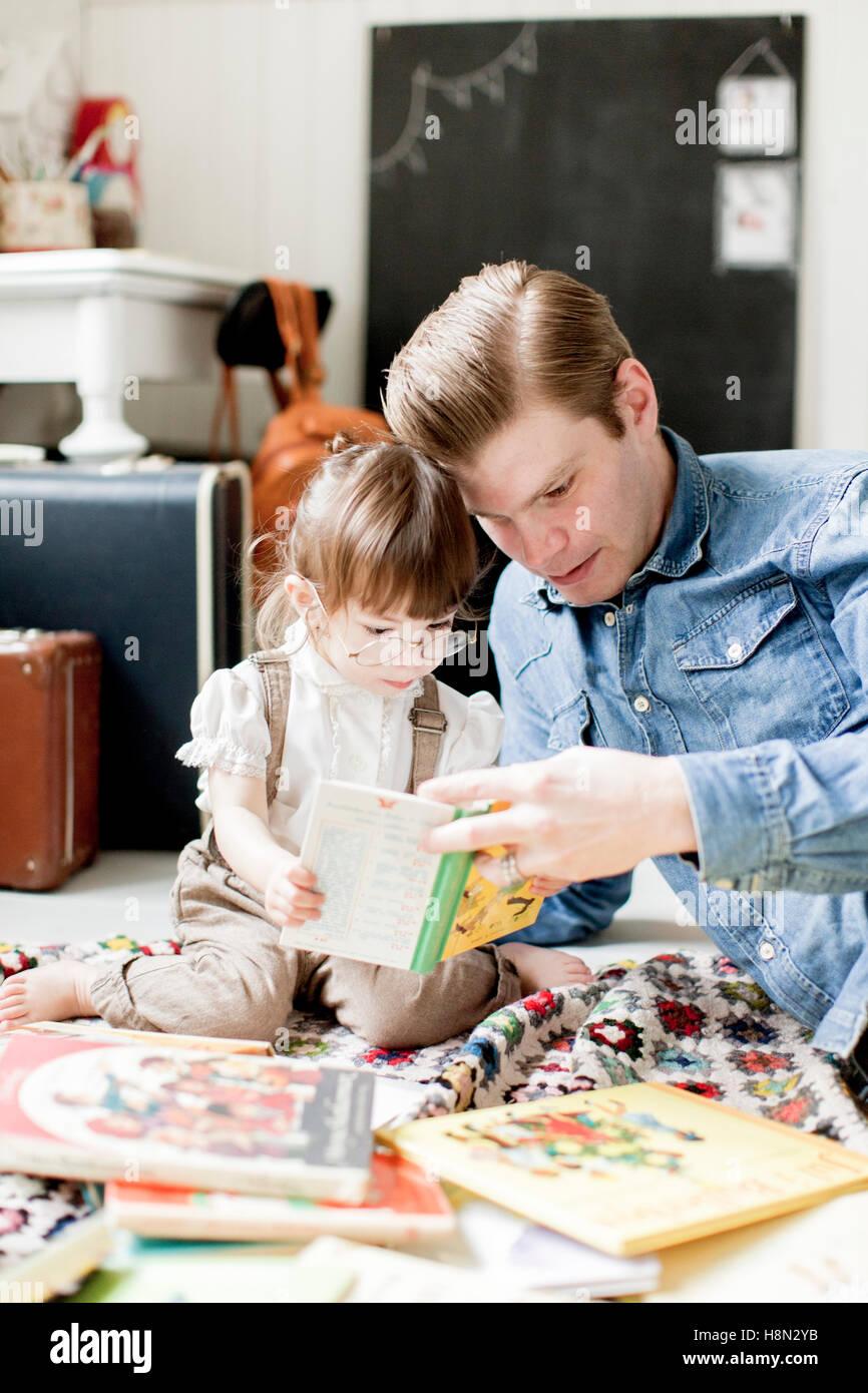 Padre lettura picture book con la figlia (2-3) Immagini Stock