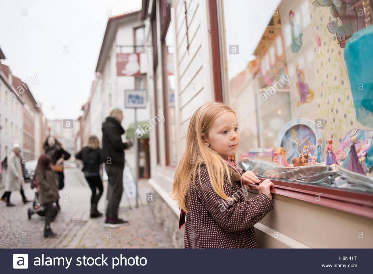 La ragazza (4-5) guardando alla vetrina di un negozio, i genitori e le sorelle (10-11, 16-17) sullo sfondo Immagini Stock