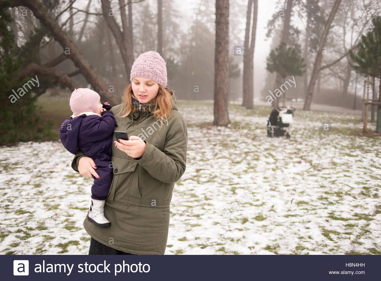 Donna giovane figlia di contenimento (12-17 mesi) e utilizzando il telefono Immagini Stock