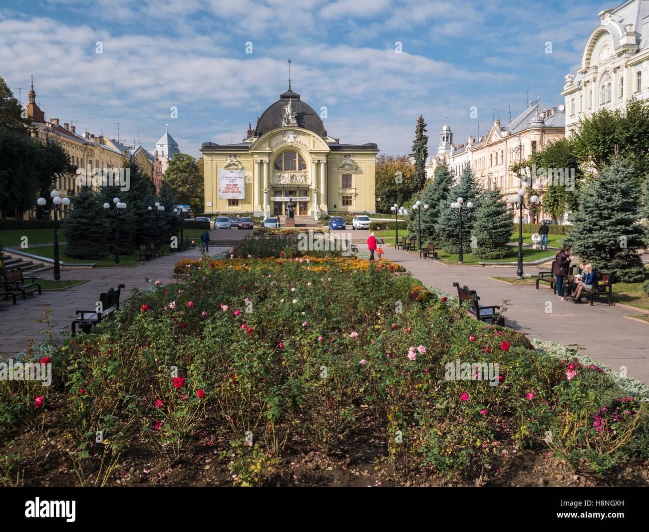 Splendidi edifici che circondano la piazza Teatralina in Chernivtsi, Ucraina. Le rose sono in fiore nel centro Foto Stock