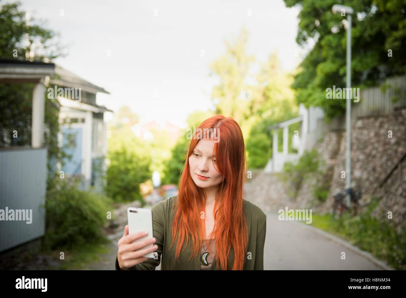 Redhaired donna usando il telefono Immagini Stock