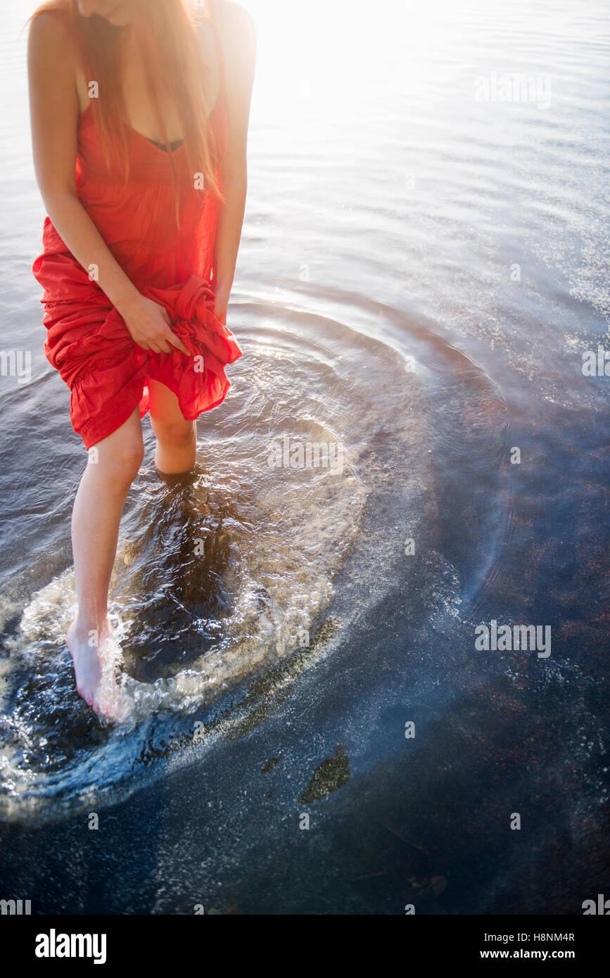 Donna in abito rosso in piedi nel lago Immagini Stock