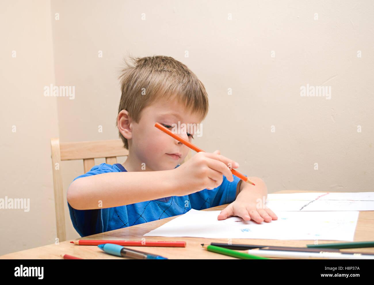 Un piccolo ragazzo di età prescolare si concentra come egli aspira a tavola in casa di famiglia. Immagini Stock