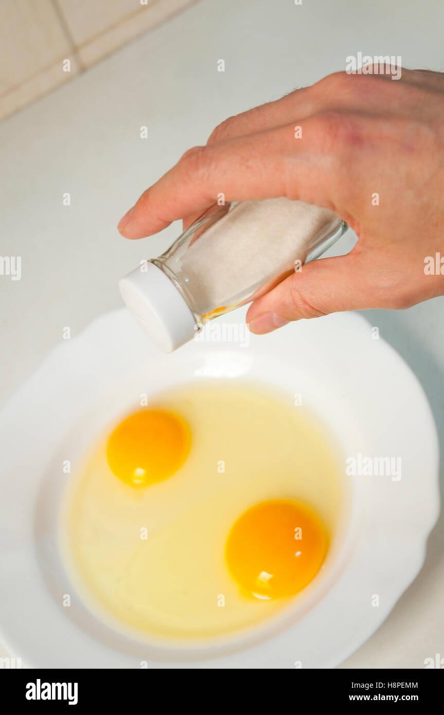 Mano d'uomo aggiungendo sale ai tuorli d'uovo. Immagini Stock