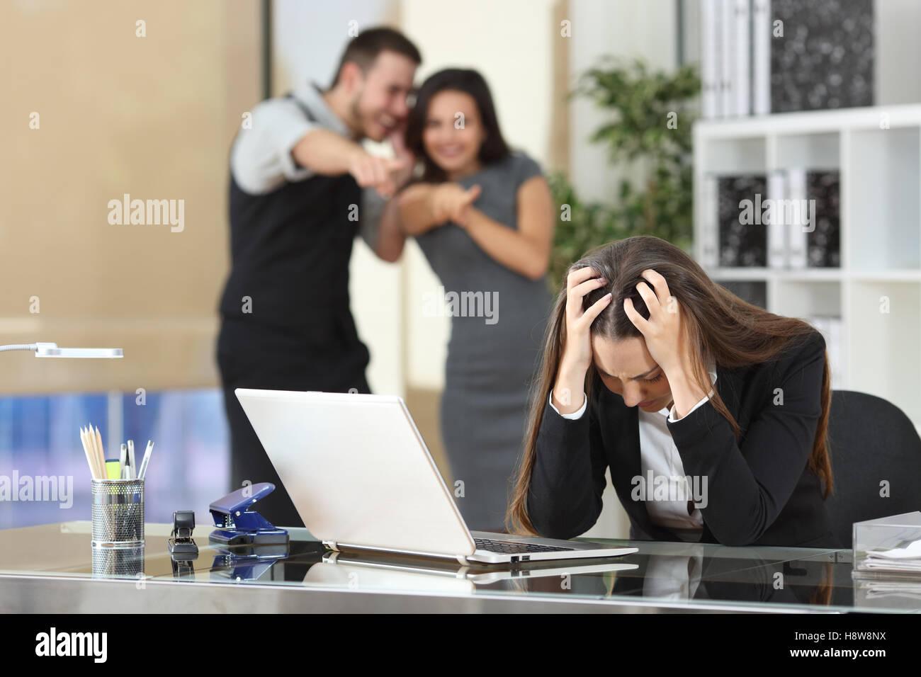 Due imprenditori bullismo un triste collega che è seduto nel suo posto di lavoro in ufficio Immagini Stock