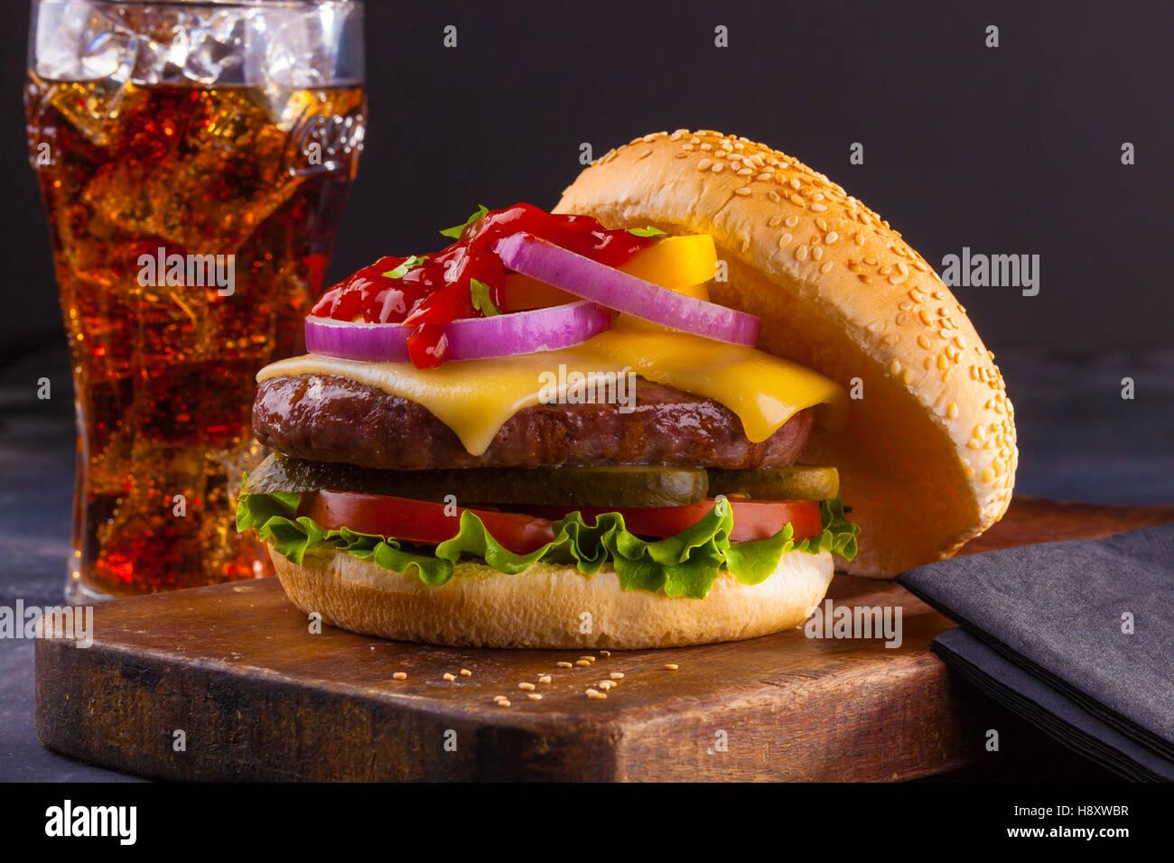 Una deliziosa casa cheeseburger con cipolle rosse, sottaceti, pomodori, lattuga e ketchup. Foto Stock