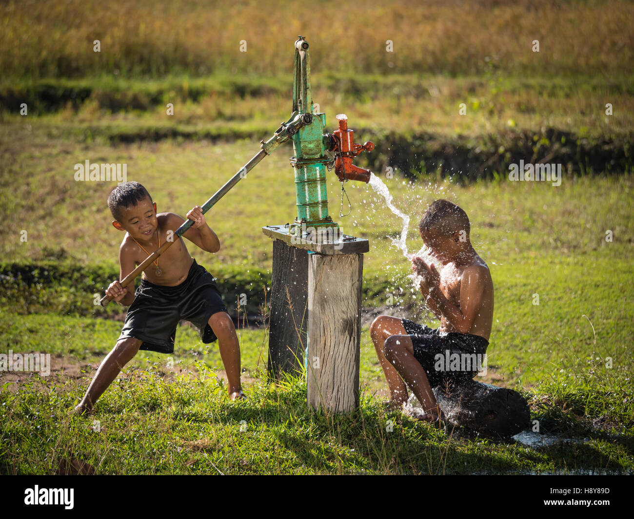Due giovani boy dondolo bagnarsi nelle acque sotterranee nei giorni caldi, campagna della Thailandia. Immagini Stock