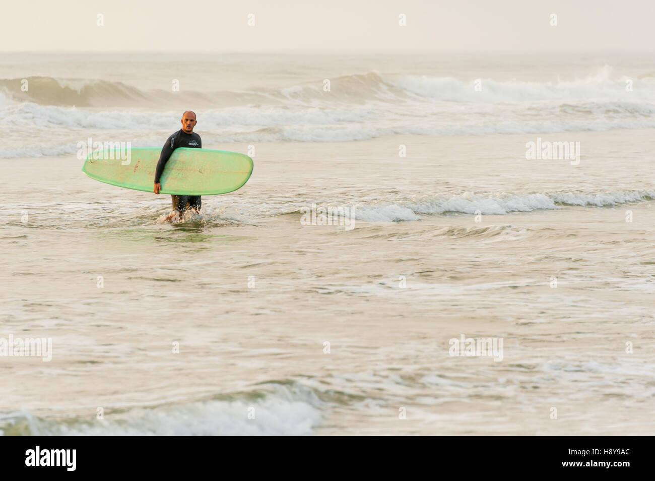 Surfer lasciando l'acqua dopo un sunrise 'dawn patrol' sessione di surf in spiaggia di Jacksonville, Florida, Stati Uniti d'America. Foto Stock