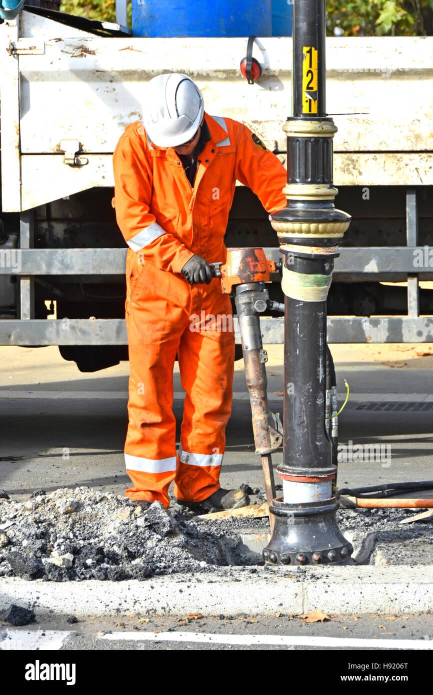 Workman lavorando su opere stradali repair job con aria compressa jackhammer strumento di attrezzature di frantumazione Immagini Stock