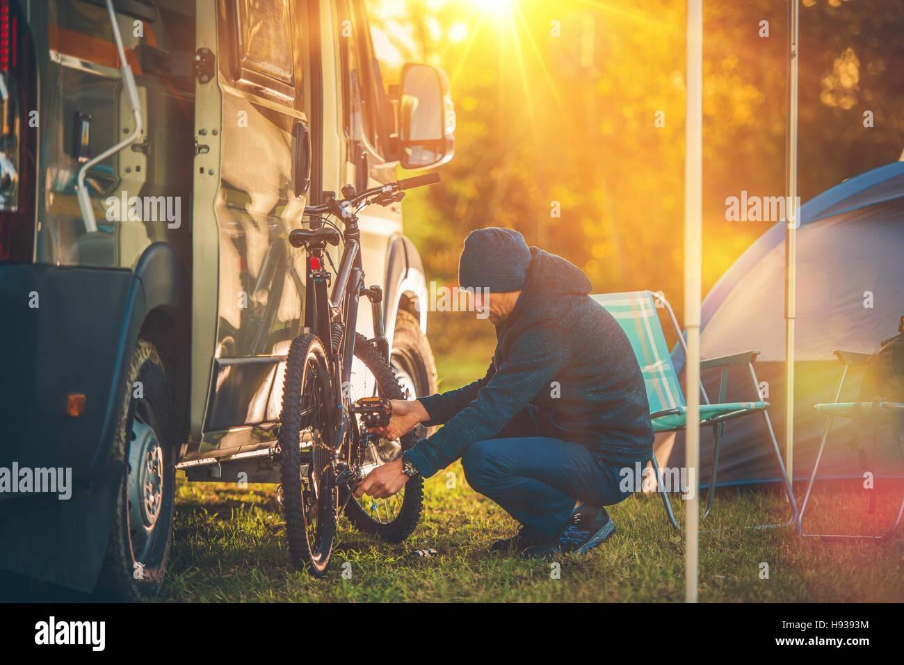 Caduta Camping tempo. Camper e tende da campeggio. Gli uomini preparando la sua Mountain Bike per un viaggio. Immagini Stock