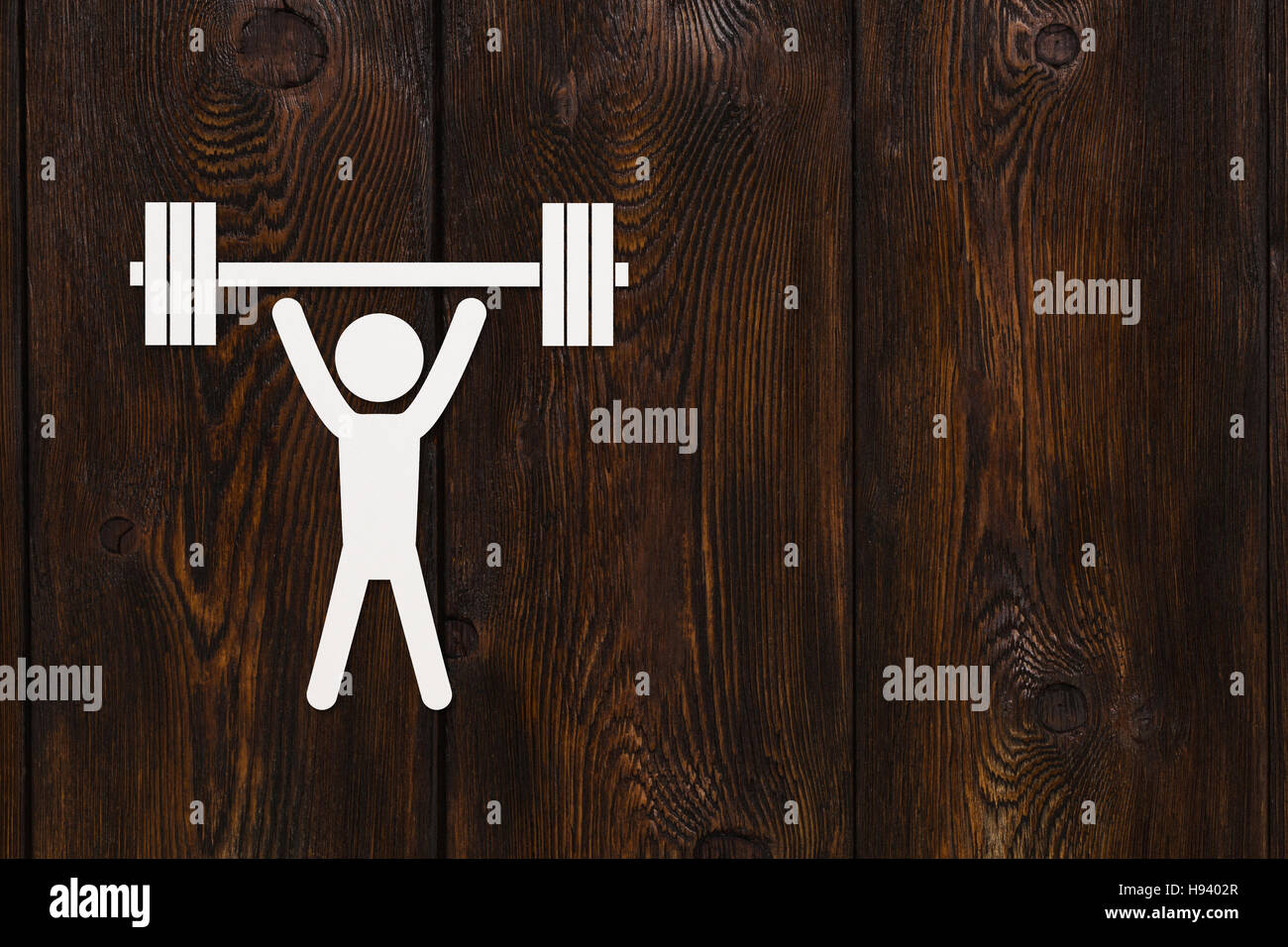 Uomo di carta con pesi. Sport e fitness concetto. Copyspace, sullo sfondo di legno Immagini Stock