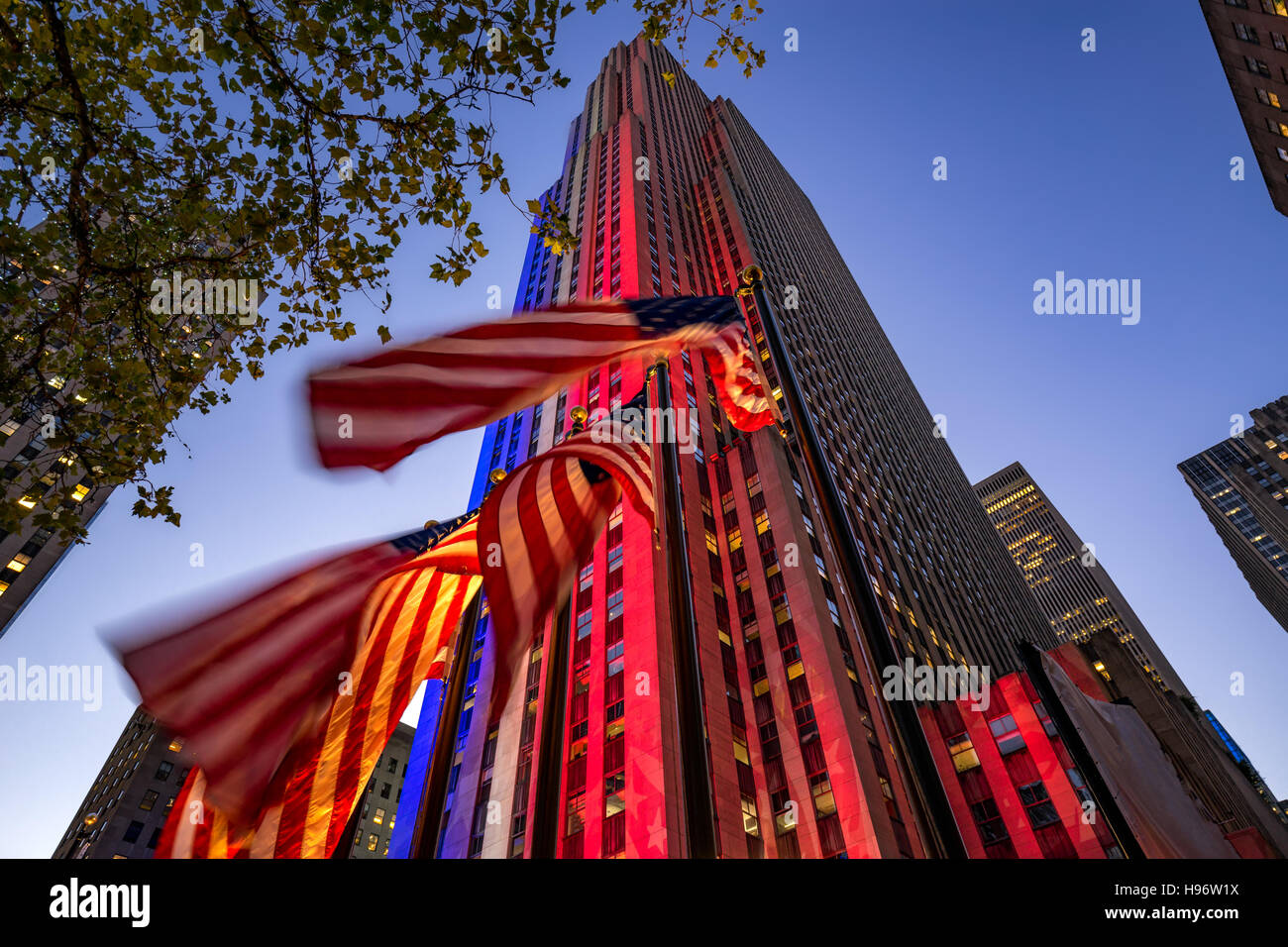 Il Rockefeller Center al crepuscolo illuminato in bianco, rosso e blu. Bandierine americane sportellino nel vento. Immagini Stock